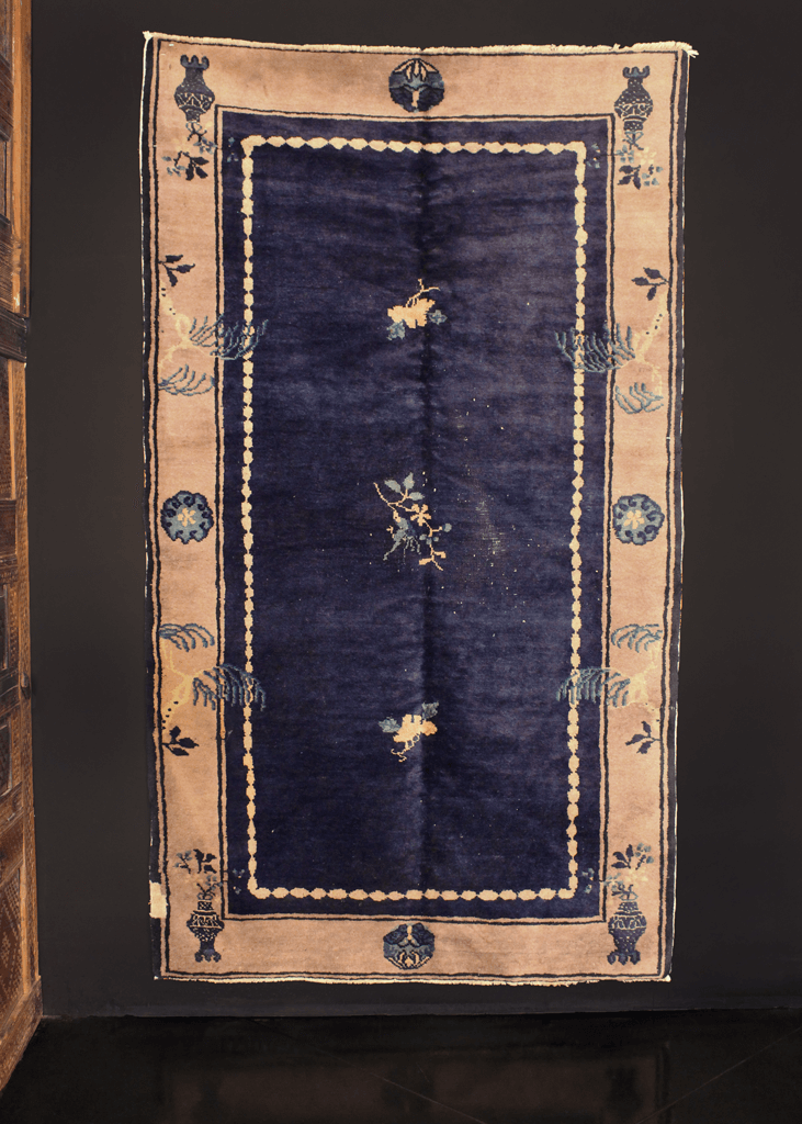 Chinese Peking rug handwoven early 20th century. Deep blue indigo field with minimal central design of flowers. Gray-ivory border with plants and flower vases.