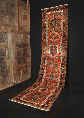 Karaja runner from Northwest Iran woven during second quarter of 20th century. Pattern of alternating geometric shapes and hooked lozenges on rust colored field. Indigo blue and greens are offset by soft ivory tones.