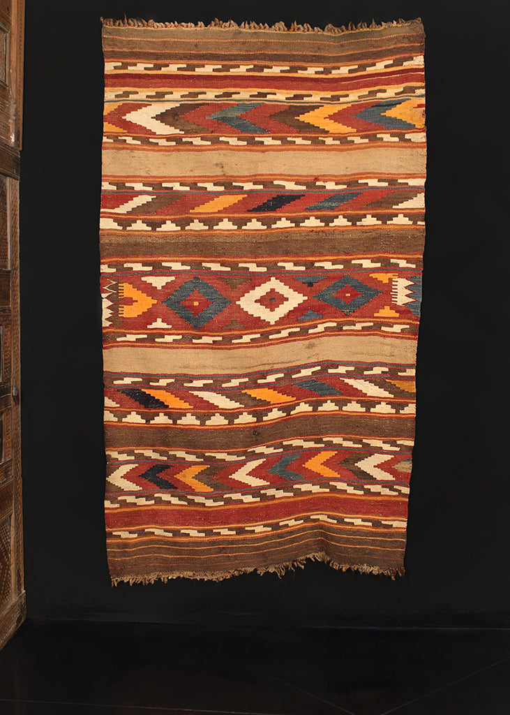Maymana kilim handwoven during second quarter of the 20th century in Northwest Afghanistan. Striped geometric design in warm red, brown, yellow and blue.