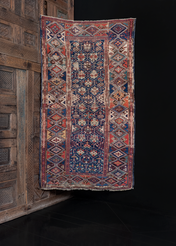 Antique shirvan rug with lattice design and geometric blossoms. Worn but in solid condition