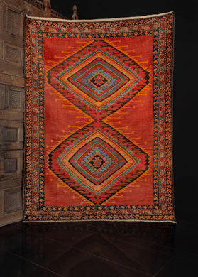 Low pile rug with a red field and multicolored concentric diamond design and floral border, in excellent condition