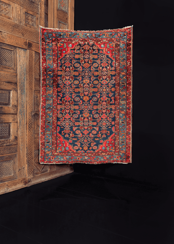 Hamadan rug from the 1930s featuring a repeating geometric pattern on a deep blue indigo field, with additional geometric or floral shapes in blues and reds