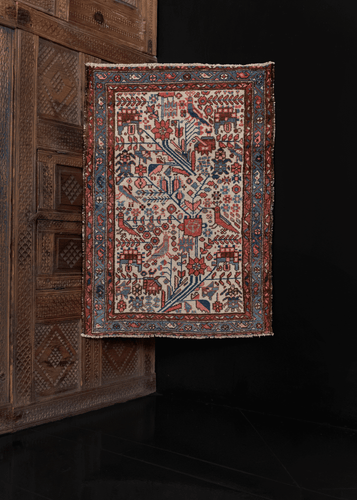 1920s Hamadan rug from West Iran in good condition with low pile and a geometric design of flowers and birds in pinks and blues on an ivory field.