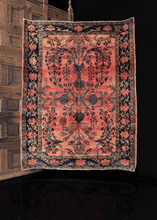 Lilihan rug with central mirrored curvilinear design in shades of blue on a peach ground