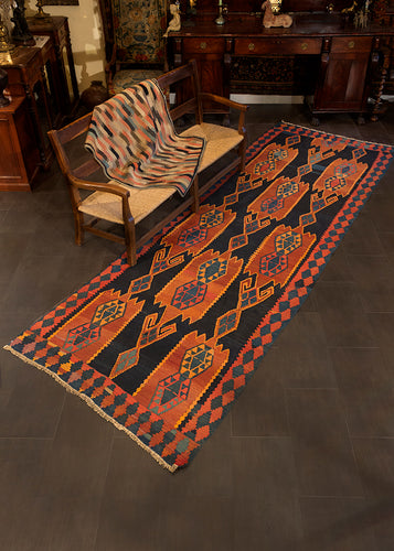 Caucasian Kuba runner handwoven during second quarter of 20th century. Geometric design, woven in a palette of indigo blue, burn orange, and soft red.