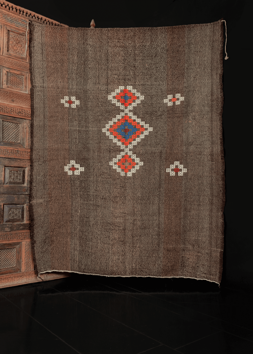 Brown kilim with goat hair and geometric shapes embroidered on top in blue orange and white