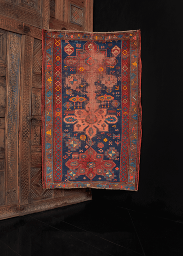 antique Kuba rug with three central medallions on an indigo blue field filled in with shapes and symbols