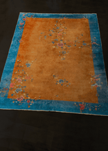 Chinese Deco rug with rust brown field and cobalt blue border with floral sprays and meanders arranged in freeform manner throughout the rug. In very good condition, signs of wear consistent with age