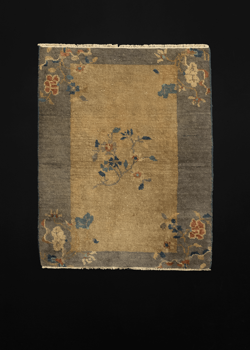 Chinese deco rug with a tan-grey field and silver grey border with floral sprays arranged in the four corners of the rug and in the center of the field.