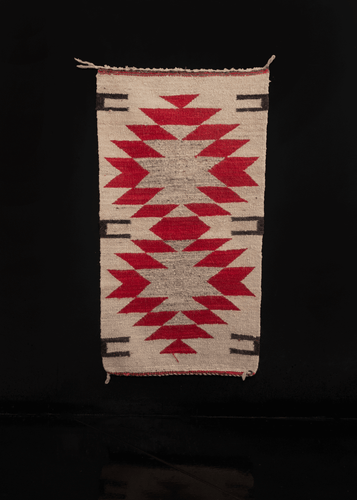 small Navajo rug with geometric design in red and grey on a cream background.