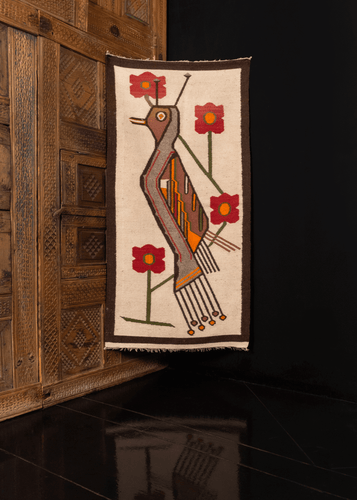 Andean textile with stylized bird and flowers on white field with thin brown border