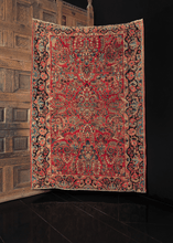antique sarouk rug with curvilinear floral design on a raspberry red field and unique borders
