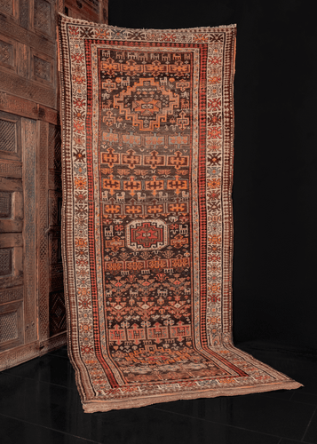 Antique Persian Kurdish runner featuring animals & symbols in bright colors like orange, pink and a grounding brown.