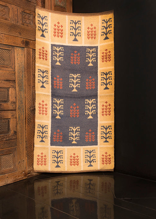 Swedish mid century shag rug. Light field encapsulated by a soft yellow main border divided by grid. Stylized trees woven in red, ivory and blue.