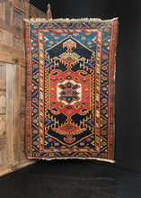 Northwest Persian rug handwoven first quarter 20th century. Mix of indigo, black, ivory and peach tones. Geometric medallion with multiple layers spanning the rug.