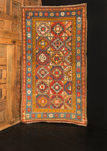 "Moghan Kazak rug handwoven during late 19th century in the Caucasus. Vibrant palette that highlight multiple ""memling gul"" medallions. Pink, bright blue and orange."
