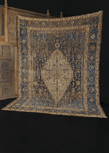 Khamseh rug from S Iran featuring a concentric diamond design with geometric shapes and symbols throughout. The color palette is composed of indigo blues and varying shades of beige.