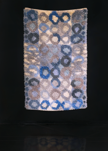 Rya shag rug handwoven in Sweden during middle of 20th century. Pattern of undulating circles in shades of blue and ray atop a backdrop of alternating ivory and blue squares.