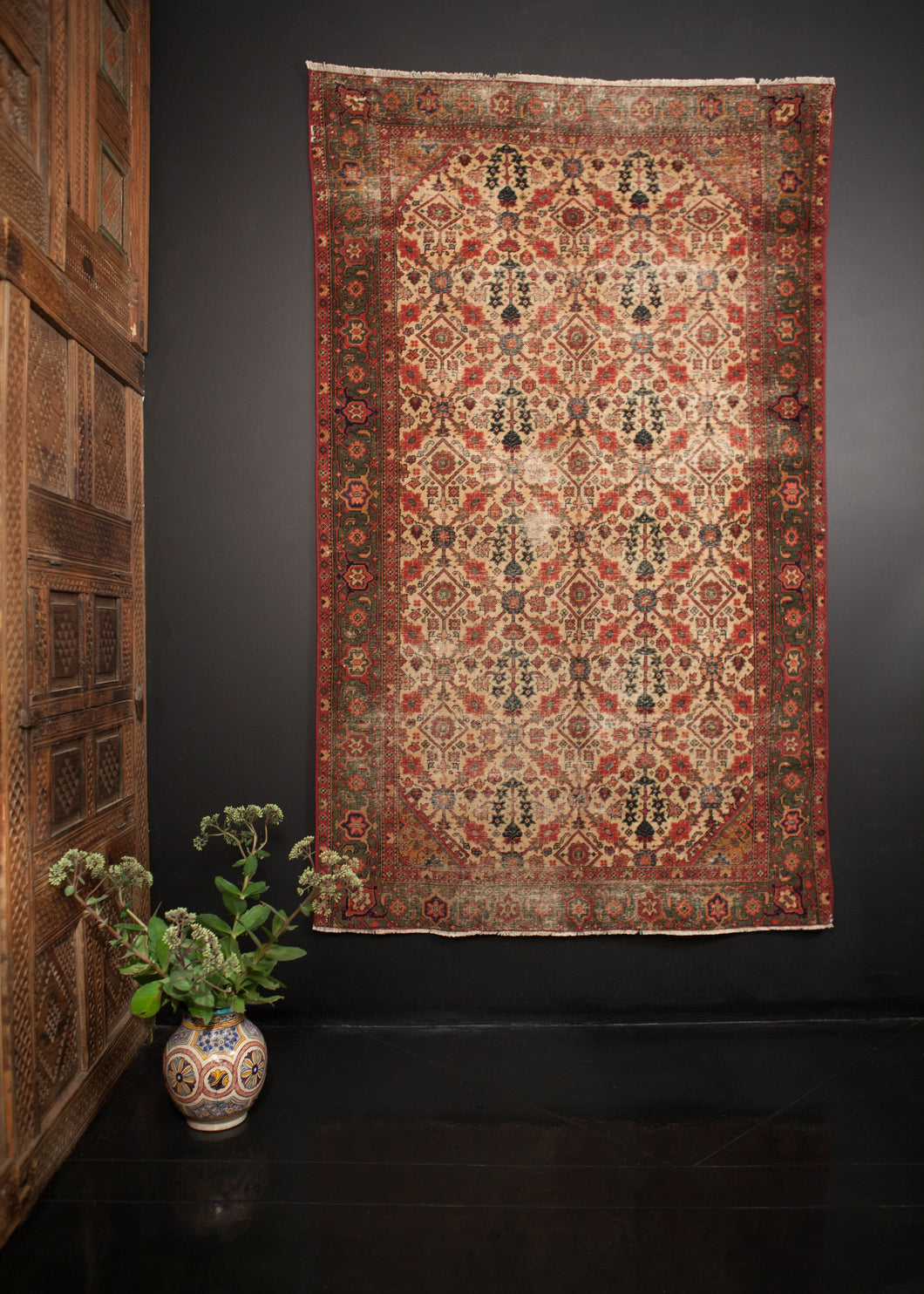 Agra rug handwoven in the early 20th century. Distinct emerald and scarlet border frame an ivory field with shades of blue and pink.