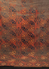 Turkmen rug dating from the 19th century. Earth color palette of brown, red, orange and navy with a repeating gul design.