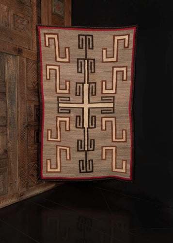 Antique Navajo rug, handwoven in the SW USA, during the first quarter of the 20th century.  This minimalistic and stunning rug features an elegant geometric design. The shapes are woven in undyed cream wool and outlined in black and brown wool. A red and black border frames the whole.   In very good condition, signs of wear consistent with age. Flatwoven, with a light handle.