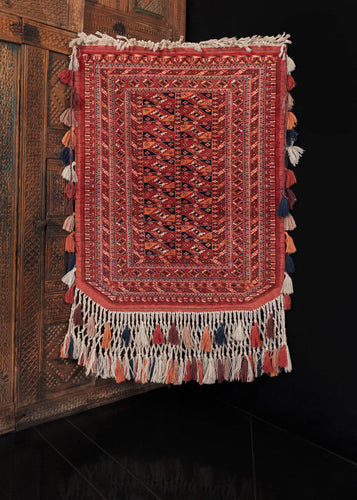 Vintage Turkmen trapping, handwoven in C Asia.   This trapping features a classic Turkmen color palette and design, with a small main field of composed of Turkmen güls, framed by six small borders all featuring classic geometric designs. The color palette is composed of earthy reds, oranges, browns, and deep blues. In excellent condition, with no signs of wear. Low pile, original fringe and tassels still intact, with a sturdy handle.