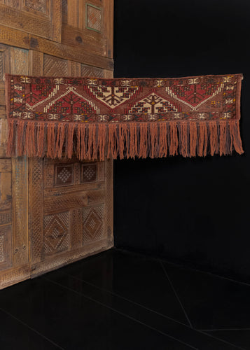 Vintage Turkmen Yomut trapping handwoven in C Asia.  This trapping features a classic Turkmen geometric design, in reds, taupes, and ivories. Splashes of deep blue and yellow provide detail and color.   In excellent condition, signs of wear consistent with age. Low pile, with original fringed end still intact, and a loose handle.