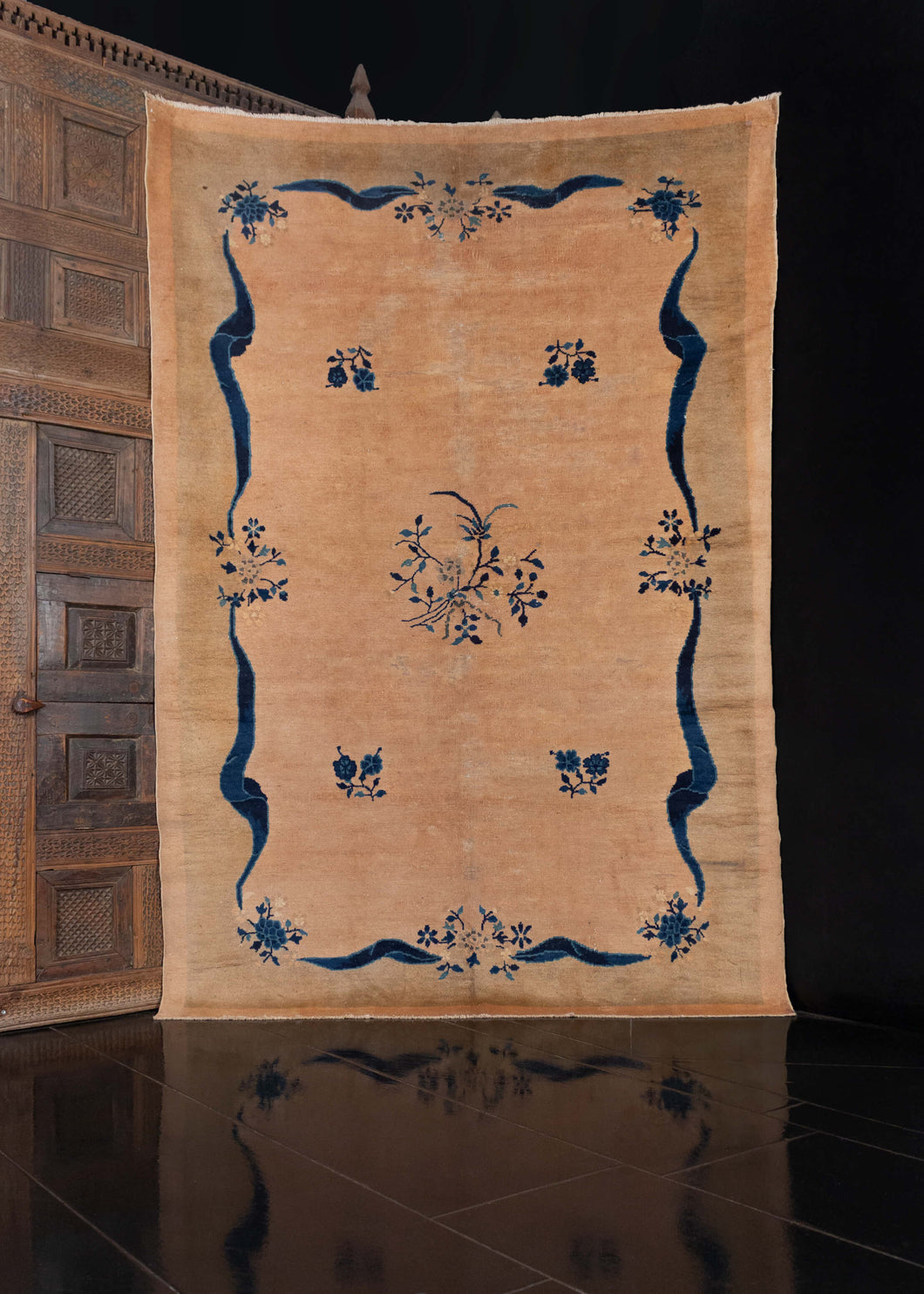 Chinese Deco rug, handwoven during the second quarter of the 20th century.   This elegant rug features a minimalist design composed of a dainty blossoms and ribbons woven in shades of indigo blue on a soft beige field. A very subtle green-beige border frames the rug and adds to the limited color palette.    In good condition, signs of wear consistent with age. Low pile, with a soft handle.
