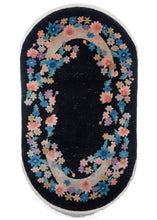 Vintage Black Oval Chinese Art Deco Rug with an open border of pastel flowers over crescent moons