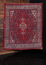 Mid-century Hamadan rug with central medallion in a red based color palette. In excellent condition, signs of wear consistent with age.