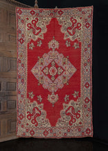 Turkish Oushak rug handwoven during the second quarter of the 20th century.  This rug features a bold central medallion and elaborate cornices, all on a bright red field. The soft mauves and ivories of the design contrast nicely with the brightness of the field, and the black outlines provide detailing to the design. The border is equally ornate as the main field composition.   In good condition, signs of wear consistent with age. Low pile, with a light handle.