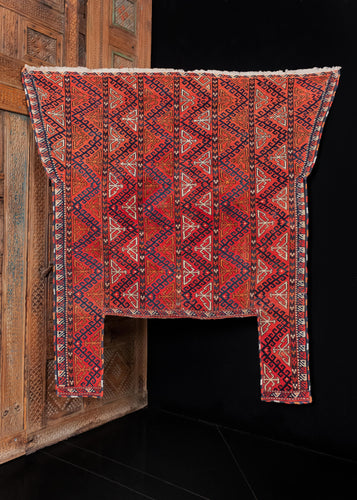 Yomud Turkmen horse-trapping, handwoven in C Asia during the first quarter of the 20th century. It features a hooked zigzag design arranged vertically in columns. The color palette is composed of the classic Turkmen colors: blues, reds, whites, and browns, with a bright orange providing a pop of color. The fine and dainty border follows the shape of the weaving and is non-contiguous. Notice the multicolor edging that alternates between red, blue, white, and orange.