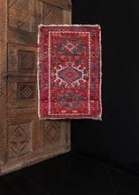 Small Karaja rug handwoven in NW Persia during the second quarter of the 20th century.   The design is composed of three medallions on a deep red field. The rest of the field is filled in with various shapes and geometric designs. The border, which is composed of a geometric floral meander. The color palette includes reds, blues, white, and oranges, while the shapes are outlined in black.   In good condition, signs of wear consistent with age. Low pile, with a sturdy handle.
