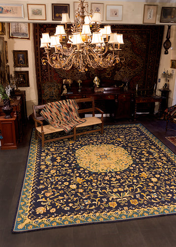 Portuguese needlework rug from second quarter of 20th century. Ornate floral pattern in yellow, brown and green on indigo blue field.