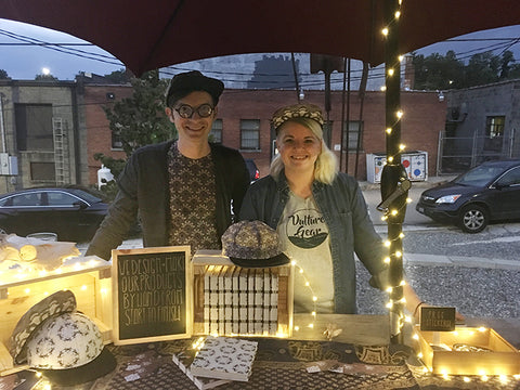 Alex and Liz behind their booth at the Moonlit Market at Burial Beer Co showing off their handmade hats and books
