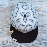Black and white flat bill hat with circular inverted vertebrae photographic pattern