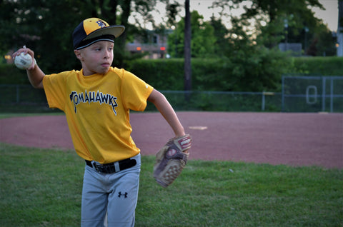 Young boy in baseball uniform throwing ball while wearing  protective headwear - 2nd Skull Skull Cap