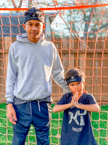 Two young boys standing in front of a soccer net wearing  protective headwear - 2nd Skull Headband
