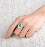 Luxury Emerald Gemstone surrounded by Diamonds on a White Gold Ring