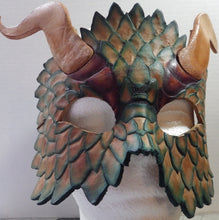 Hand carved scales highlight the mask