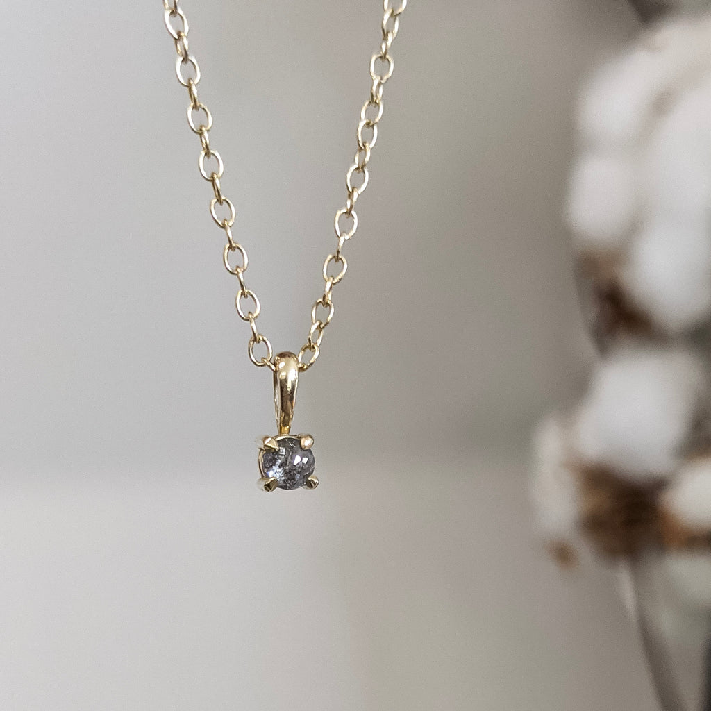 Yellow gold necklace with salt and pepper diamond with white flowers in the background
