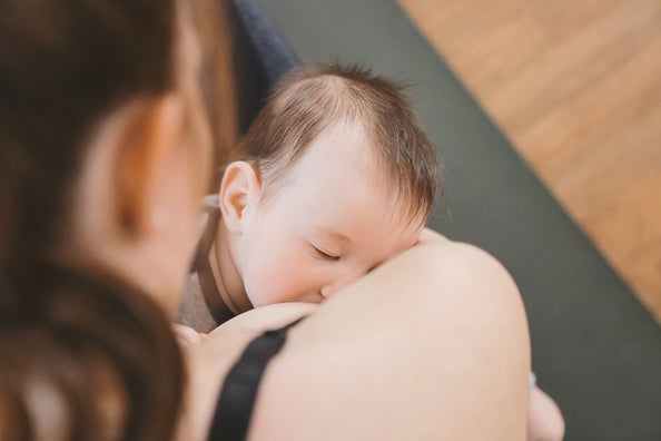 How can we minimize back pain and improve posture while breastfeeding?