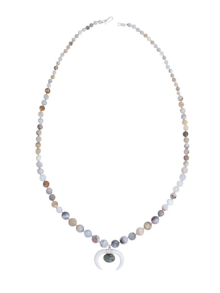 Women wearing a necklace rental from Chan Luu called African Opal Graduated Pendant Necklace
