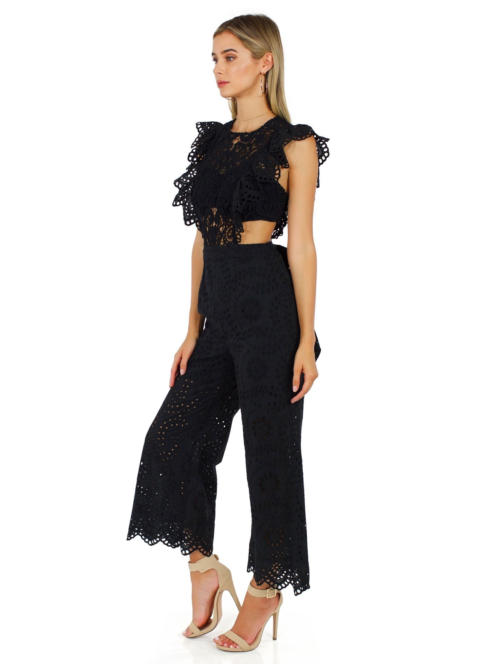 Woman wearing a jumpsuit rental from Nightcap Clothing called Eyelet Apron Jumpsuit