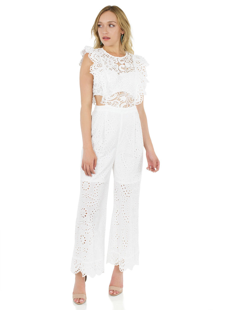 Women wearing a jumpsuit rental from Nightcap Clothing called Nightcap Eyelet Apron Jumpsuit