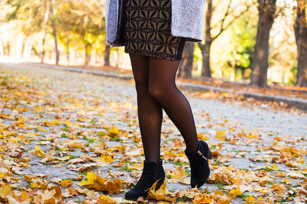 Black hosiery and booties walking in fall leaves