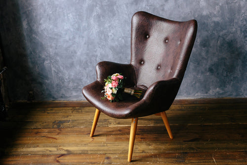 bouquet lying on brown armchair