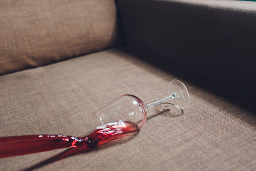 red wine spilled on grey couch