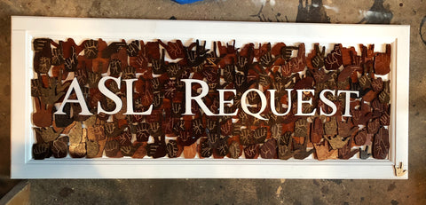 "Wooden sign of ""ASL Request Est 2013"" on brown handshapes pieces"