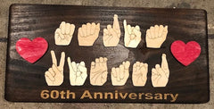 "Wooden sign with handshapes ""Maria Victor"" with hearts on side and engraved wording ""60th Anniversary"""